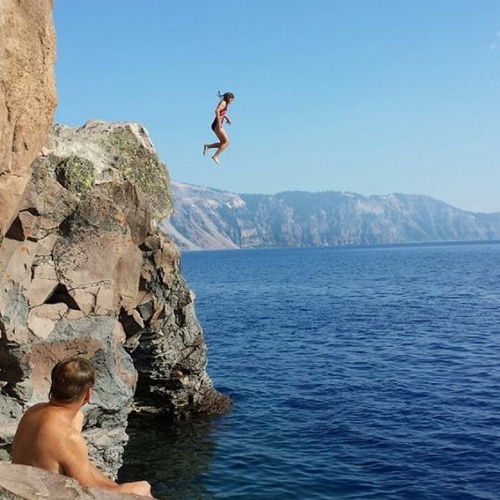 Person jumping off cliff into water